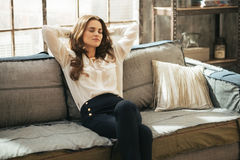 Relaxed young woman sitting in loft apartment royalty free stock image