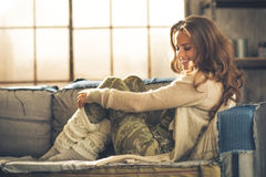 Relaxed young woman sitting in loft apartment Stock Image