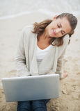 Relaxed young woman sitting on lonely beach with laptop. Relaxed young woman in sweater sitting on lonely beach with laptop royalty free stock images