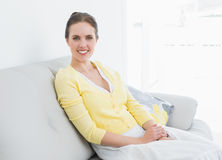 Relaxed young woman sitting on sofa at home Stock Images