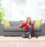 Relaxed young woman sitting by a sofa Stock Images