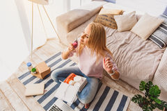 Relaxed young woman smelling perfume. Top view of serene girl is enjoying scent of cologne. She is sitting on floor in living room and carrying box of cosmetic stock images