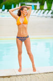 Relaxed young woman standing at poolside Royalty Free Stock Photography