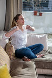 Relaxed young woman stretching her arms on sofa, waking up royalty free stock photography