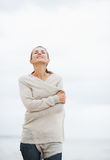 Relaxed young woman in sweater walking on lonely beach Royalty Free Stock Photography