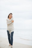 Relaxed young woman in sweater walking on lonely beach Royalty Free Stock Images