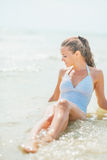 Relaxed young woman in swimsuit enjoying sitting in sea water Stock Images