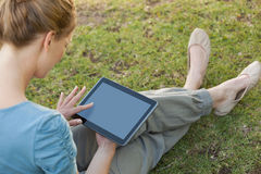 Relaxed young woman using digital tablet at park Stock Photos