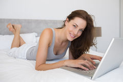 Relaxed young woman using laptop in bed Stock Images