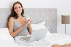Relaxed young woman using laptop in bed Stock Photo
