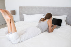 Relaxed young woman using laptop in bed Royalty Free Stock Photo