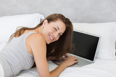Relaxed young woman using laptop in bed Stock Image