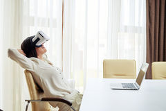 Relaxed young woman in virtual reality glasses Royalty Free Stock Photos