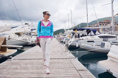 Relaxed young woman walking in marina Stock Photos