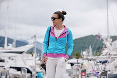 Relaxed young woman walking in marina Stock Image