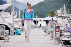 Relaxed young woman walking in marina Royalty Free Stock Image