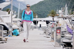 Relaxed young woman walking in marina Royalty Free Stock Photo