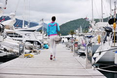 Relaxed young woman walking in marina Stock Photo