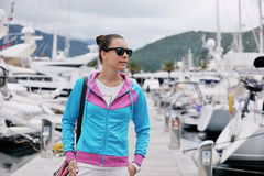 Relaxed young woman walking in marina Royalty Free Stock Photos