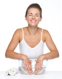 Relaxed young woman washing hands in glass bowl with water Stock Image