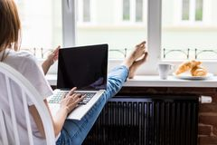 Relaxed young woman working laptop with legs on widnowsill with morning breakfast stock photos