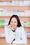 Relaxed young woman working in pharmacy Stock Image