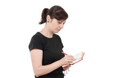 Relaxed young woman writing notes. Over a white background Stock Image
