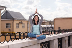 Relaxed young woman in a yoga pose on the parapet Stock Photo