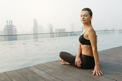 Relaxed young yoga woman in yoga pose near pool. Royalty Free Stock Photo