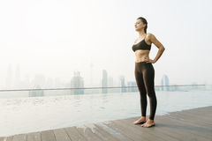 Relaxed young yoga woman in yoga pose near pool. Stock Photography