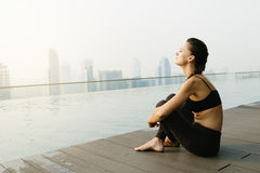 Relaxed young yoga woman in yoga pose near pool. Stock Image
