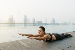 Relaxed young yoga woman in yoga pose near pool. Stock Photos
