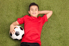 Relaxed youngster lying on pitch and holding a football Stock Photography