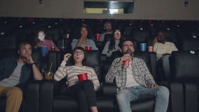 Relaxed youth enjoying movie in cinema eating popcorn drinking having fun. Relaxed youth men and women are enjoying movie in cinema eating popcorn drinking stock video