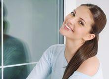 Relaxin bonito da jovem mulher em casa na camiseta confortável Imagem de Stock Royalty Free