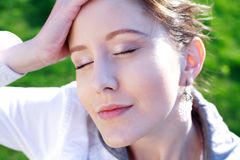Relaxing 1. Beautiful young woman relaxing with closed eyes, greeen background Royalty Free Stock Photo