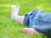 Relaxing. In the grass with a flower between the toes Royalty Free Stock Image