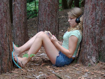 Relaxing. Girl, with headphones, leaning against tree in woods reading a book Stock Photos