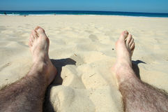 Relaxing. Man hairy legs on beach, water and people in background Stock Images