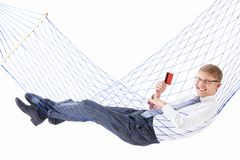 Relaxing. Young businessman with credit card in a hammock isolated stock image