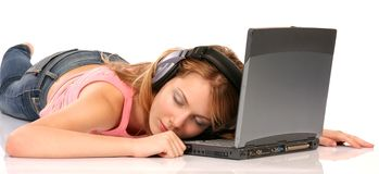 Relaxing. Young beautiful woman with laptop and headphones, isolated on white Stock Images