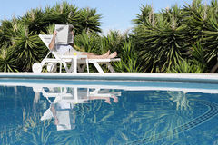 Relaxing. Man relaxing and lazing at pool Royalty Free Stock Photo