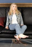 Relaxing. Beautiful blond model sitting on couch relaxing Stock Images