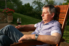 Relaxing. Man relaxing in the Italian sun with a glass of wine royalty free stock image