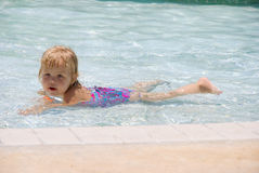 Relaxing. Adorable little blond girl relaxing in the pool Stock Photos