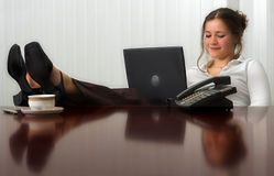 Relaxing. Young woman with laptop in meeting room, with her feet on the table Royalty Free Stock Photo