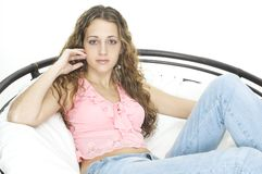 Relaxing. A pretty young teenager relaxes in a large round chair Stock Image
