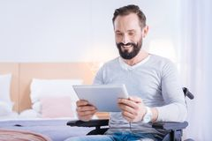 Happy paralyzed man holding a tablet Royalty Free Stock Image