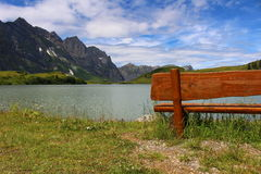 Relaxing at an Alpine Lake. Bench at Trübsee, a lake above Engelberg in the foot of Mount Titlis Royalty Free Stock Photography