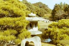 Relaxing ancient Japanese stone lantern in Shinjuku Gyoen National Garden, Tokyo, Japan. Shinjuku Gyoen National Garden is a popular Japanese garden in Tokyo Stock Photo